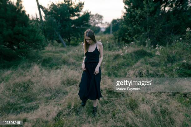 young woman standing in long grass in long black dress - 黒のドレス ストックフォトと画像