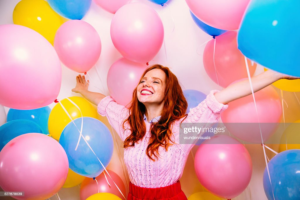 Young Woman Standing In Many Balloons : Stock Photo