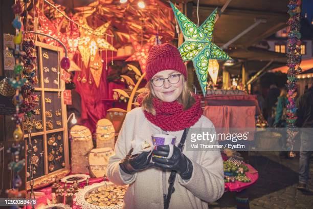 young woman standing in market during christmas - val thoermer stock-fotos und bilder