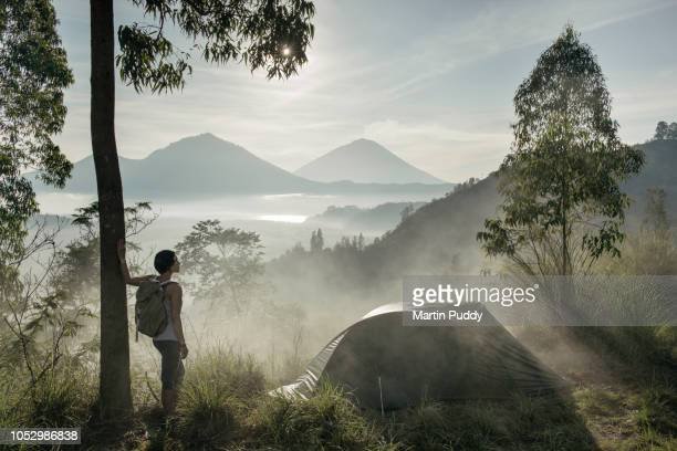 young woman standing in mist, next to tent, looking at the view while camping - キャンプ 1人 ストックフォトと画像