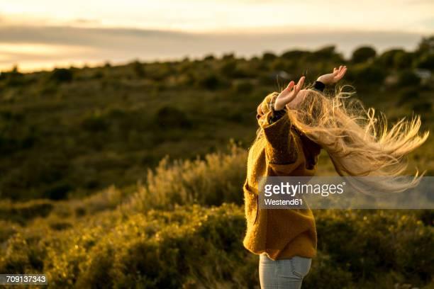 young woman standing in nature raising her arms - motivación fotografías e imágenes de stock