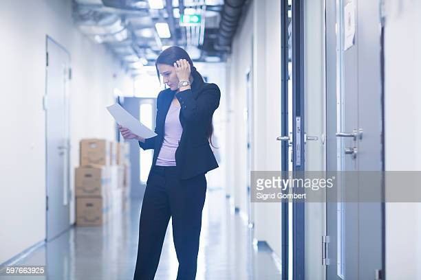 young woman standing in office corridor looking down at paperwork scratching head - sigrid gombert stock pictures, royalty-free photos & images