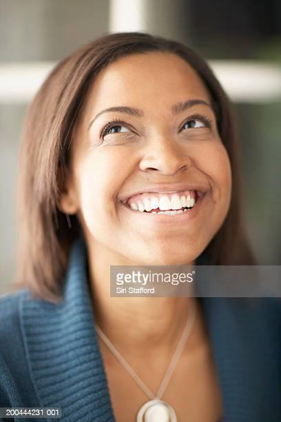 Young woman standing in open doorway, smiling