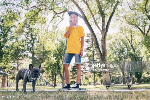 young woman standing in park with skateboard and her dog - yellow shoe stock pictures, royalty-free photos & images