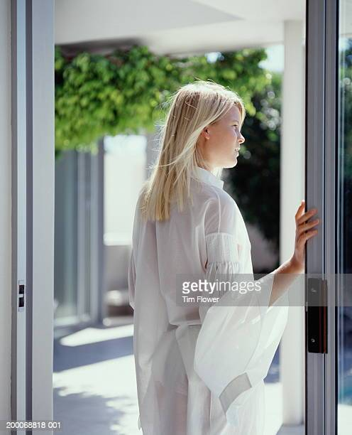 young woman standing in patio doorway, rear view - french doors stock pictures, royalty-free photos & images