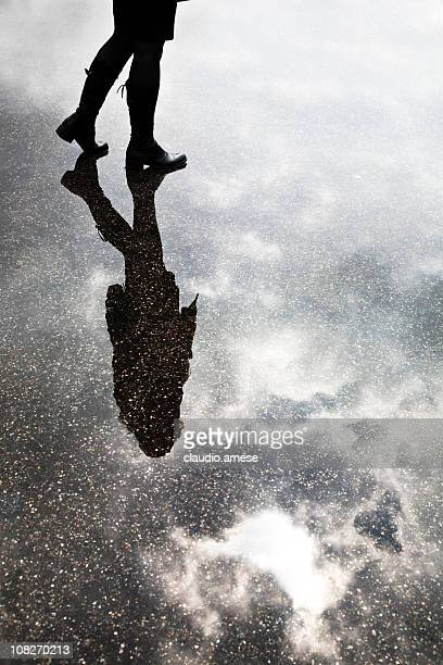 Young Woman Standing in Puddle with Reflection of Sky.