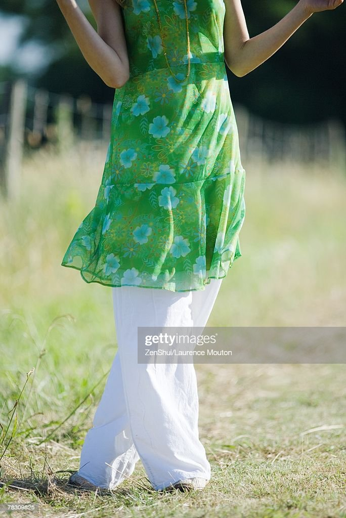 Young woman standing in rural field with legs crossed at knees, cropped view : Stock Photo