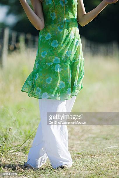 young woman standing in rural field with legs crossed at knees, cropped view - tunic stock pictures, royalty-free photos & images