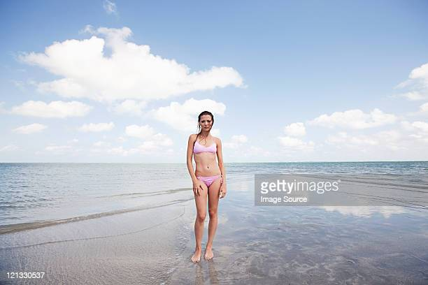 Young woman standing in shallow sea, portrait