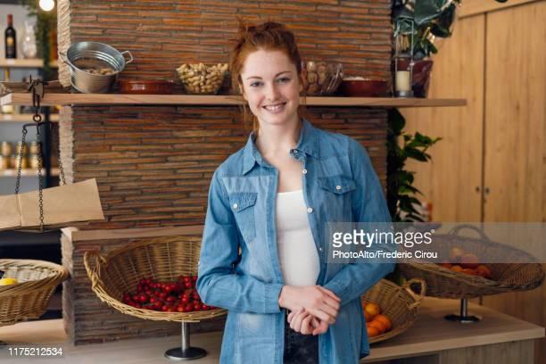 young woman standing in shop - デニムシャツ ストックフォトと画像