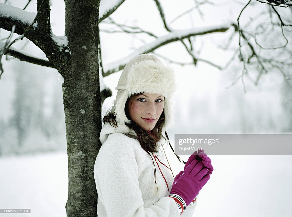 Young woman standing in snow, leaning against tree, portrait : Stock Photo