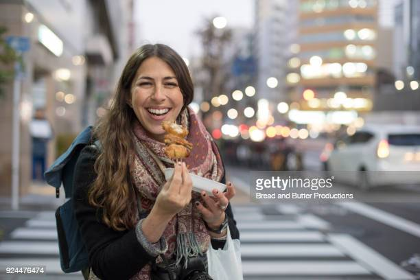 young woman standing in street eating yakatori chicken from street vendor iin tokyo, japan - butter chicken stock photos and pictures