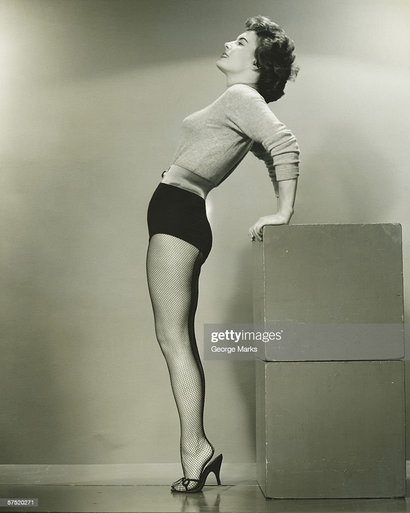 Young woman standing in studio, leaning backwards, (B&W) : Stock Photo