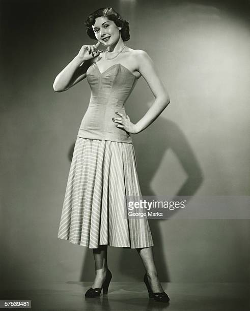 young woman standing in studio, smiling, (b&w) - corset stock pictures, royalty-free photos & images