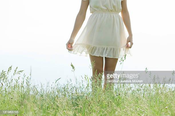 young woman standing in tall grass, cropped - minirock stock-fotos und bilder