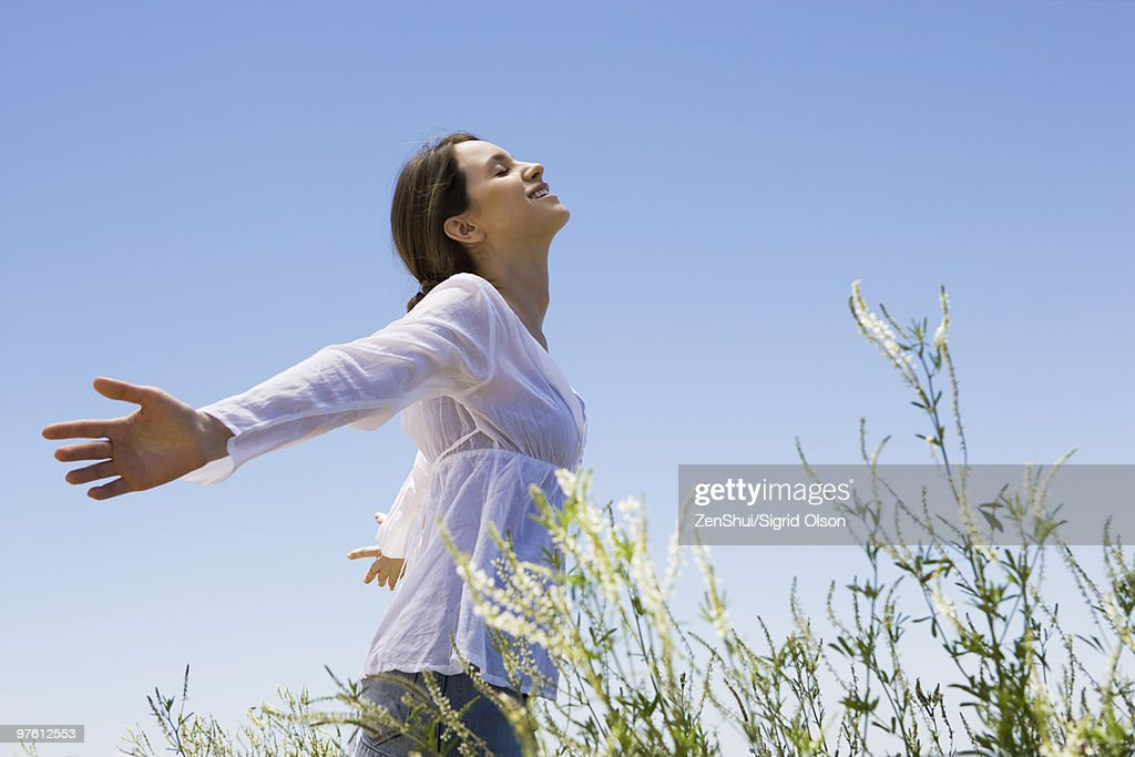 Young woman standing in tall grass with arms out, eyes closed : Foto de stock