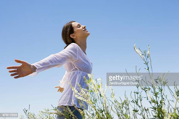 young woman standing in tall grass with arms out, eyes closed - non urban scene stock pictures, royalty-free photos & images
