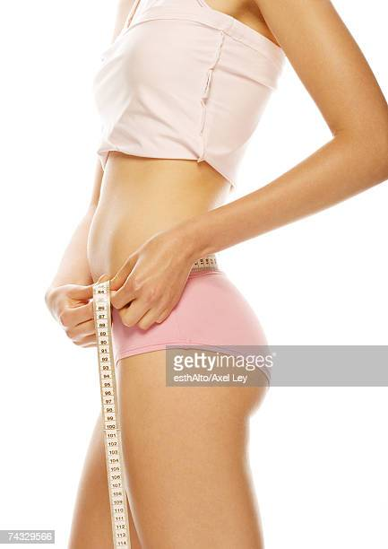 young woman standing in tank top and underpants, measuring waist - skinny teen stock photos and pictures