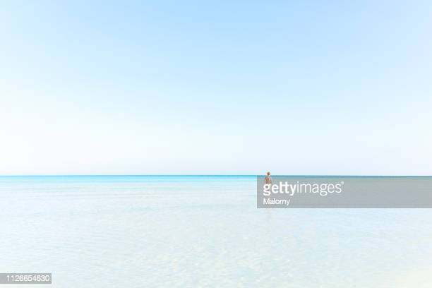 young woman standing in the ocean on a sandbar near the beach - holbox island fotografías e imágenes de stock