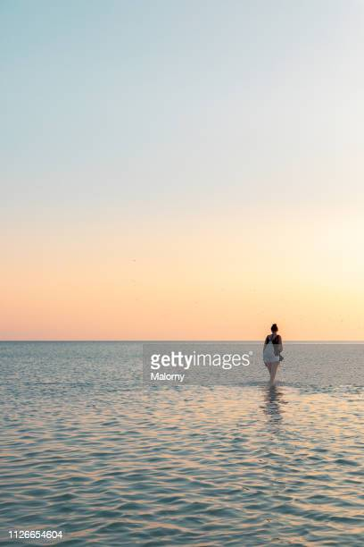 young woman standing in the ocean. sunset on a summer day. - holbox island fotografías e imágenes de stock