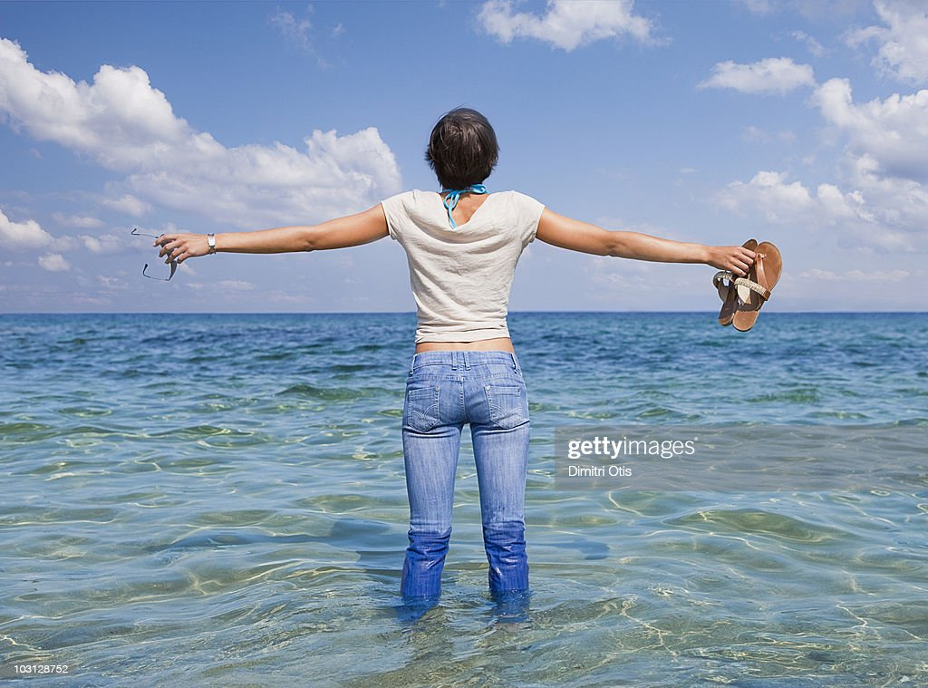 Young woman standing in the ocean wearing jeans : Stock Photo