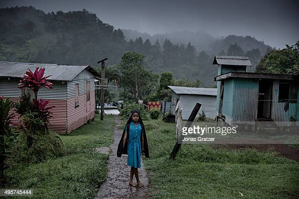 A young woman standing in the rain in the village Naviavia which has just been bought from Fiji by Kiribati to ensure that Kiribati islanders have a...