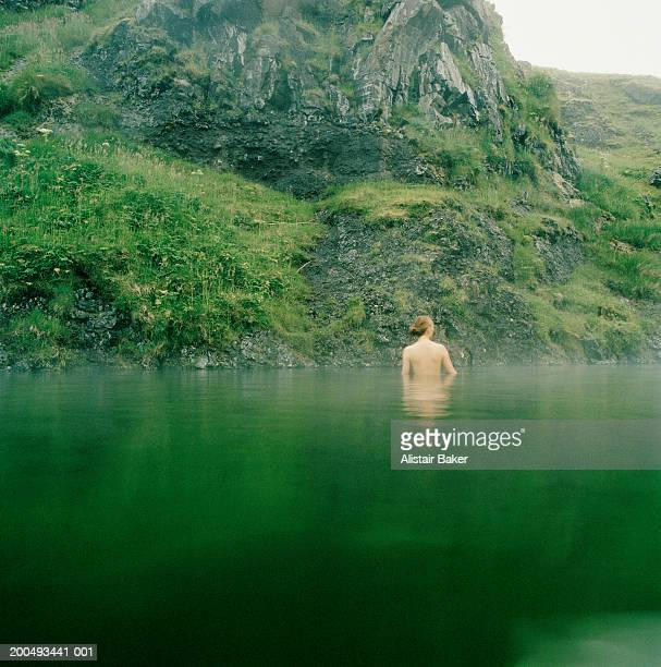 Young woman standing in thermal pool, rear view