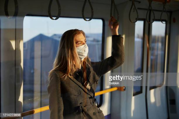 young woman standing in train wearing protective face mask - social distancing stock-fotos und bilder