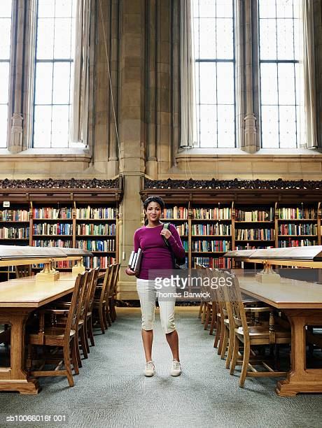 Young woman standing in university library, smiling