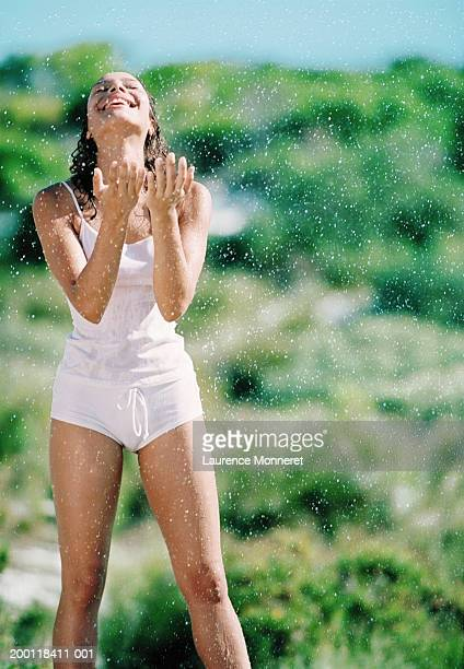Young woman standing in water spray, eyes closed, laughing