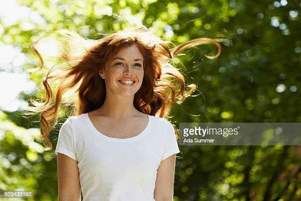 Young woman standing in wind smiling
