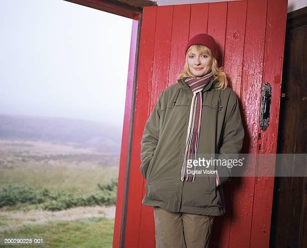 Young woman standing indoors by doorway, smiling, portrait