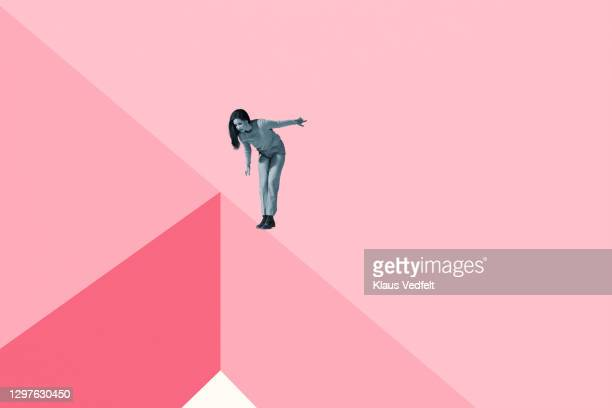 young woman standing looking down from ledge of pink blocks - junge frau rätsel stock-fotos und bilder
