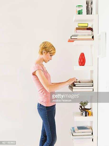 Young woman standing near bookshelf
