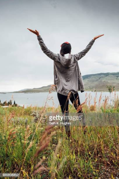 young woman standing near dillon reservoir, arms raised, rear view, silverthorne, colorado, usa - silverthorne stock photos and pictures