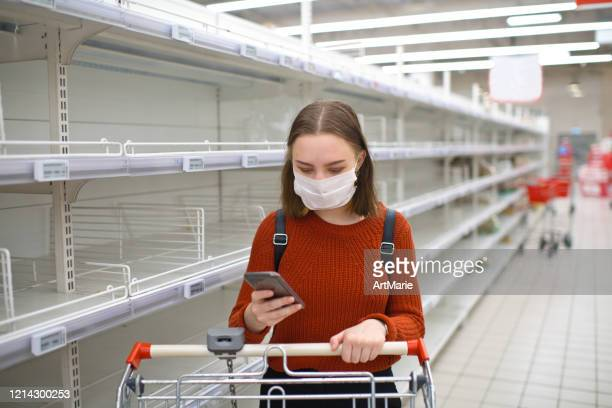 young woman standing near empty shelf in a supermarket and using smartphone - market retail space stock pictures, royalty-free photos & images