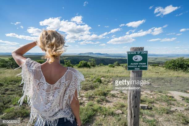Young woman standing near lion warning sign