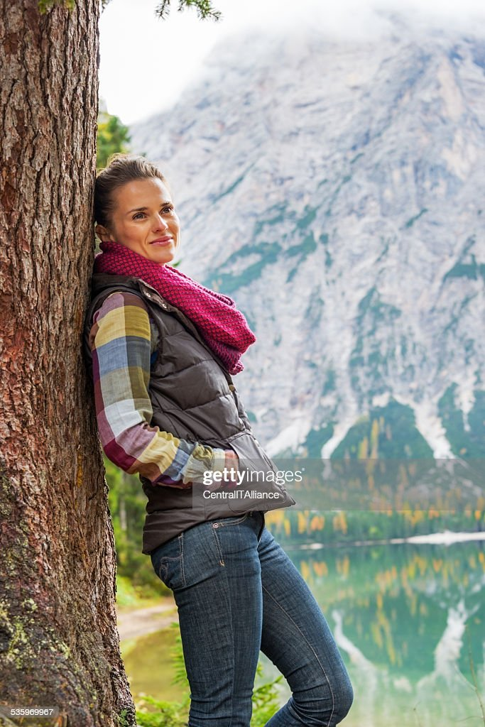 Young woman standing near tree on lake braies, italy : Stock Photo