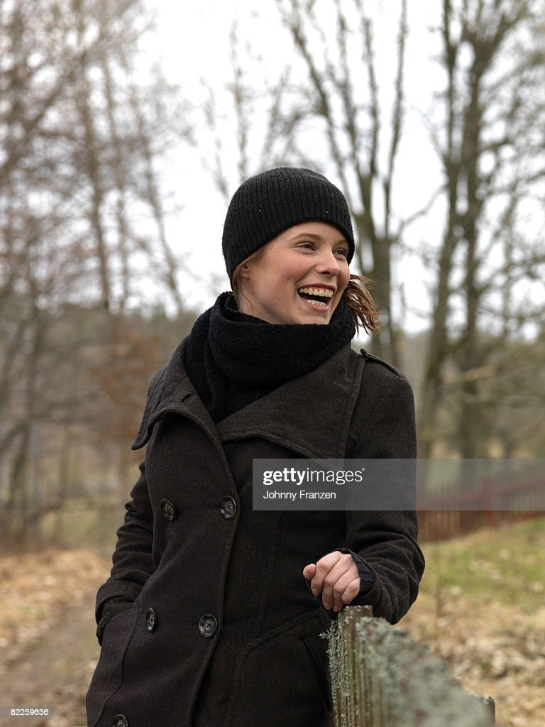 A young woman standing next to a fence Sweden. : Stock Photo
