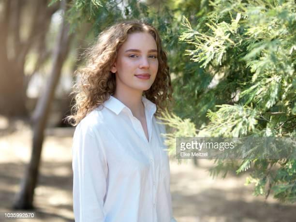 young woman standing next to a tree - innocence - fotografias e filmes do acervo