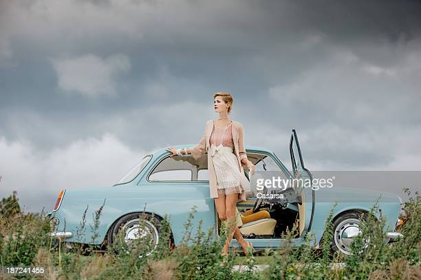 Young woman standing next to a vintage car
