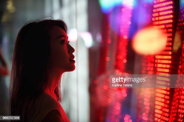 Young woman standing next to a window with red light