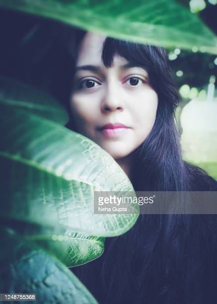 young woman standing next to frangipani tree - neha gupta stock pictures, royalty-free photos & images