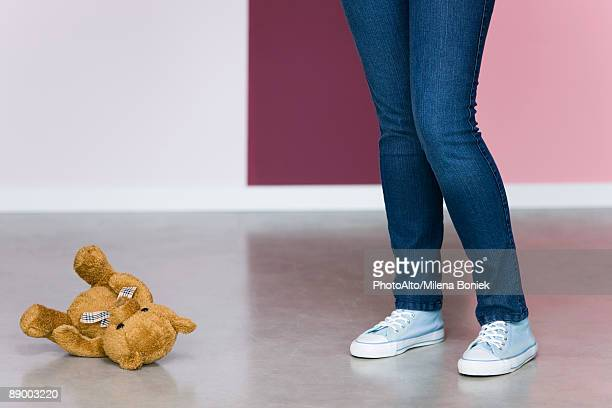 Young woman standing next to teddy bear on floor, low section