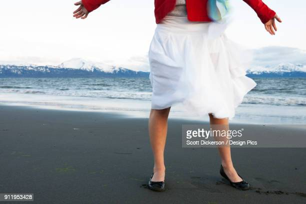 a young woman standing on a beach at the waters edge with arms outstretched wearing a white skirt and red jacket - home run ストックフォトと画像