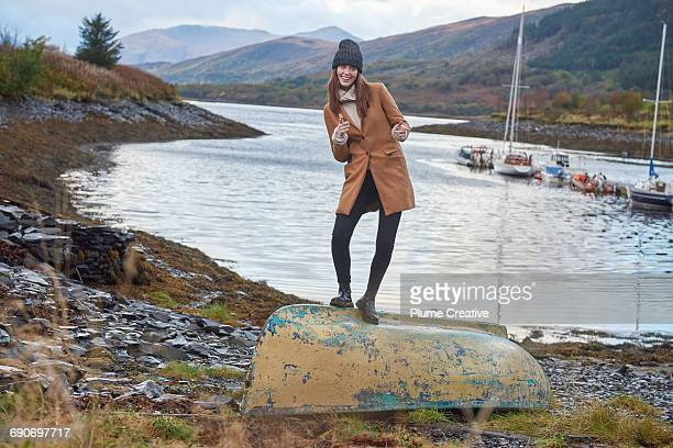 Young woman standing on a boat being silly