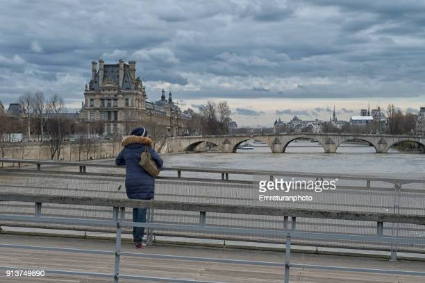 young woman standing on a bridge on seine river and watching the cityscape ,paris. - emreturanphoto stock pictures, royalty-free photos & images