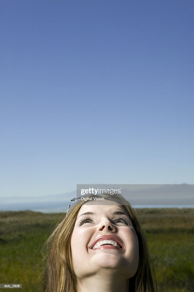 Young woman standing on a grassy field looking up smiling : Foto de stock