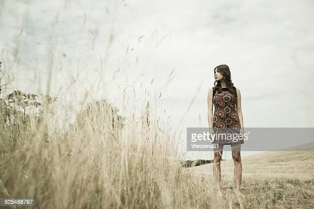 Young woman standing on a harvested meadow