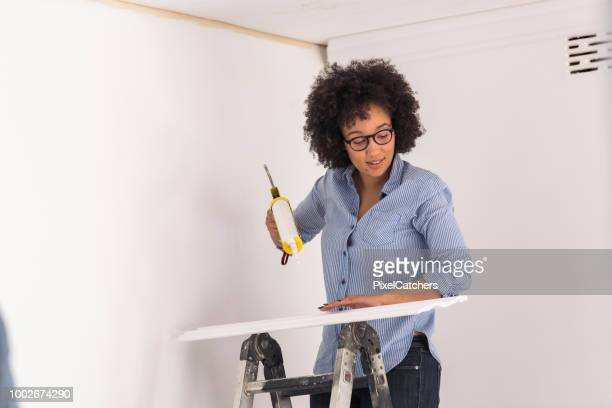 young woman standing on a ladder applying adhesive to new cornice - architectural cornice stock photos and pictures